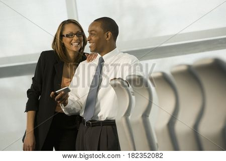 African business people laughing with cell phone