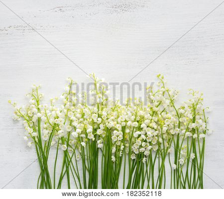 Lilies of the Valley on white shabby wooden background