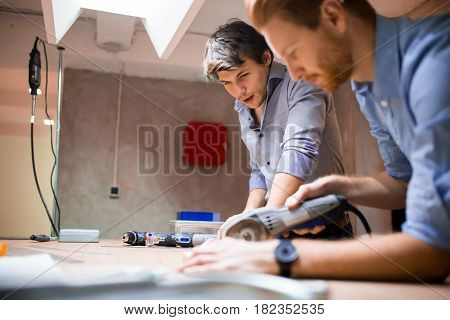 Two designers working together in workshop with precision tools