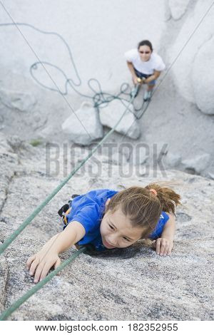 Asian mother and daughter rock climbing