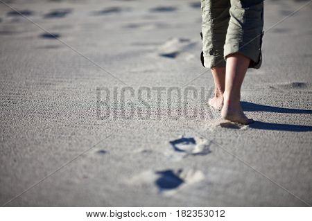 Woman walking on the beach. Close up shot of her legs and footprints. Kangaroo island, South Australia.
