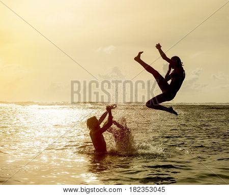 Silhouette of young girl jumping out of the ocean which throws strong two man on the background of the expiring sunset. Single shooting