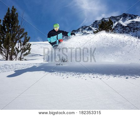 Freerider snowboarder moving down in snow powder at the ski resort