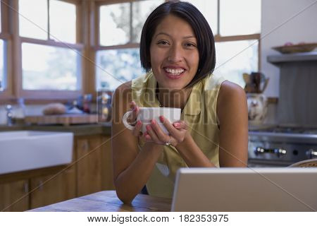 Native American woman drinking coffee and using laptop