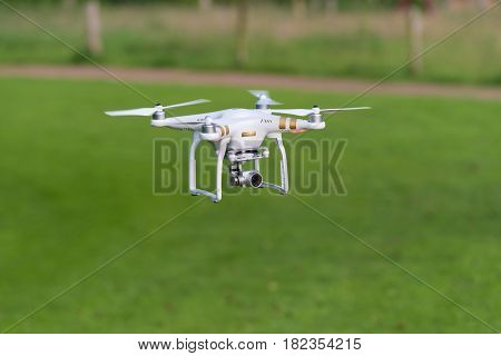 OLDENZAAL NETHERLANDS - JUNE 19 2016: DJI Phantom drone with camera attached flying low above the grass