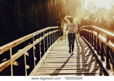 Young female jogger exercising outdoors in nature