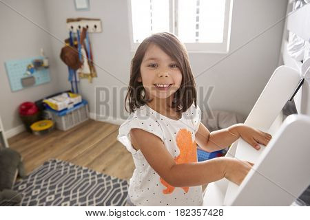 Portrait Of Girl Climbing Ladder To Bunk Bed
