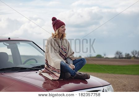 Woman siting on off road vehicle hood