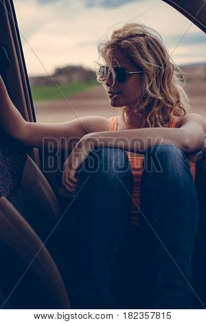 Female driver sitting in off road vehicle on road trip