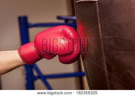 Close-up hand of boxer at the moment of impact on punching bag over gym background