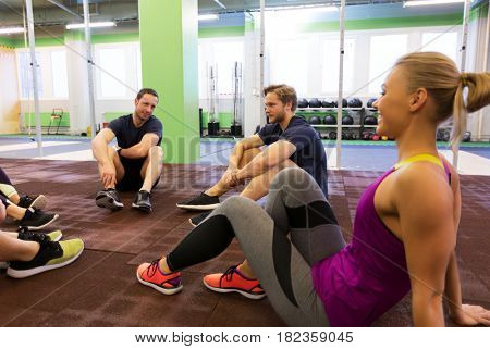 fitness, sport, exercising and healthy lifestyle concept - group of happy people resting in gym