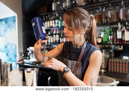 drinks, people and luxury concept - barmaid with shaker pouring alcohol from bottle into jigger and preparing cocktail at bar