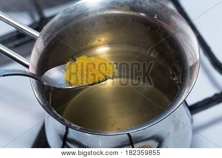 Adding brown sugar to melted gelatin in metal pot. Macro. Photo can be used as a whole background.