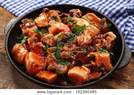 Delicious chicken cacciatore in frying pan on kitchen table
