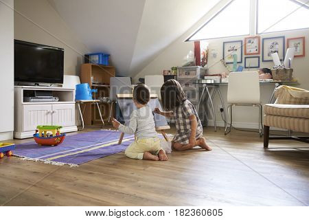 Boy And Girl Drawing On Chalkboard In Playroom