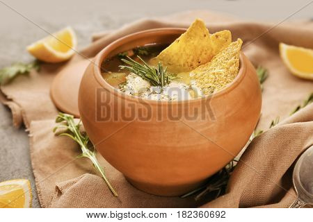 Crock pot with chicken soup and nachos on table