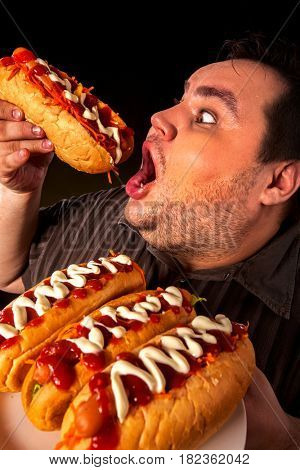 Diet failure of fat man eating fast food hot dog on plate. Close up of breakfast for hungry overweight person who spoiled healthy food. Junk meal leads to obesity.