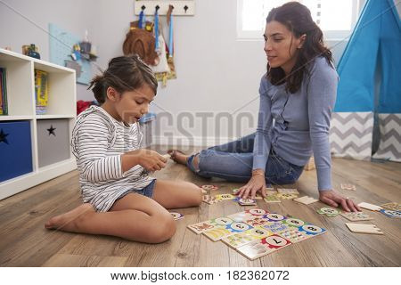 Mother Playing Number Puzzle Game With Daughter In Playroom