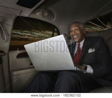 African man using laptop in car