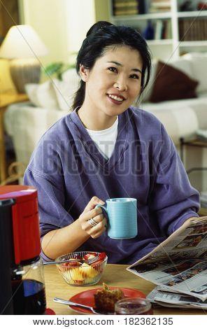 Korean woman having breakfast with newspaper