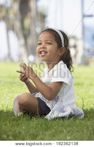 Young mixed race girl sitting cross-legged in grass