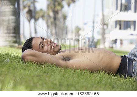 Young mixed race man with bare chest laying on grass