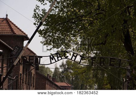 An Inscription Above The Main Gate To Concentration Camp In Auschwitz - Arbeit Macht Frei.