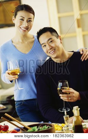Asian couple drinking wine in kitchen