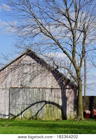 old faded red barn in farm setting with tree shadow and orange vintage lawn chairs