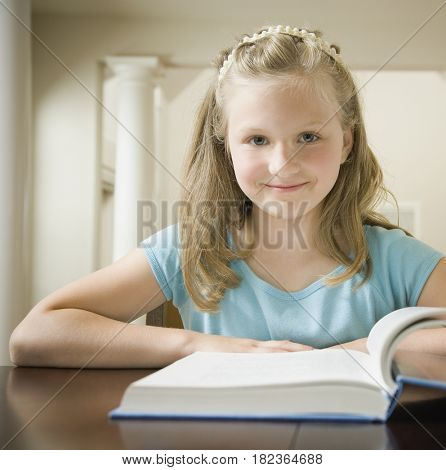 Girl smiling with book at table