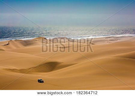 Magical jeep - safari through the huge sand dunes on the ocean shore. Atlantic coast of Namibia, south of Africa. The concept of exotic and extreme travel