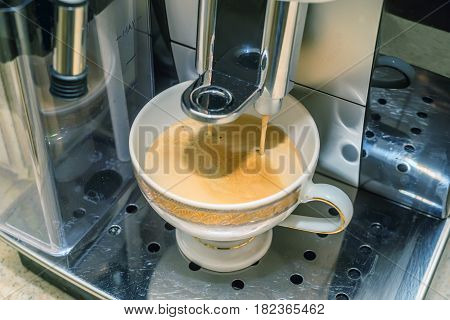 Using coffee maker to prepare coffee. Pouring espresso coffee from coffee machine