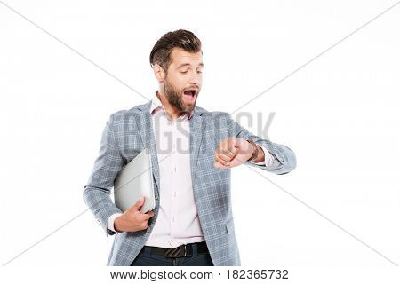Image of screaming young man standing isolated over white background and holding laptop computer. Looking at watch.