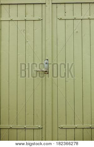 Details in traditional achitecture concept. Closeup of big green oldfashioned wooden doors.