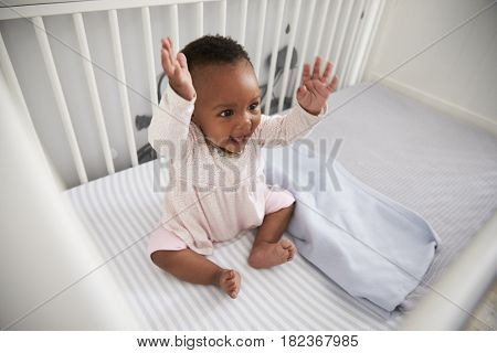 Happy Baby Girl Playing In Nursery Cot