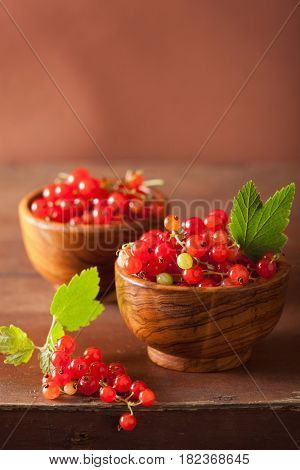 fresh redcurrant in bowls over rustic wooden background