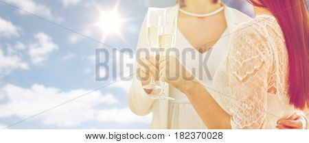 people, homosexuality, same-sex marriage, celebration and love concept - close up of happy married lesbian couple holding and clinking champagne glasses over sky and sun background