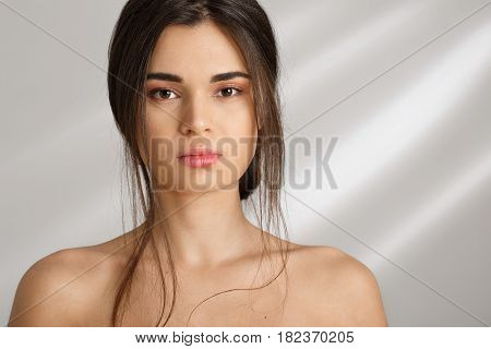 Front view. Portrait of young beautiful woman after spa. Standing naked, looking straight at camera.