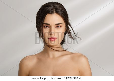 Closeup of young naked woman looking straigt. Isolated on grey background. Nature beauty. Beautiful skin.