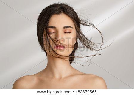 Closeup of beautiful naked woman after spa procedures enjoying herself. Eyes closed. Skin care.