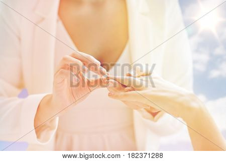 people, homosexuality, same-sex marriage and love concept - close up of happy lesbian couple hands putting on wedding ring over sky and sun background