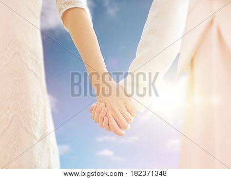people, homosexuality, same-sex marriage and love concept - close up of happy married lesbian couple holding hands over sky and sun background