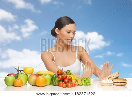 diet, healthy eating, food and people - woman with fruits and vegetables rejecting hamburger and sandwich over blue sky and clouds background