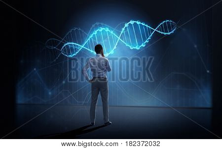 business, people, technology and science concept - businessman looking at virtual dna molecule projection over dark background from back