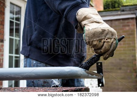Painter decorator metalworker paints metal iron railing black with baggy jumper and workman's gloves in back garden of residential job - BIY craftsman