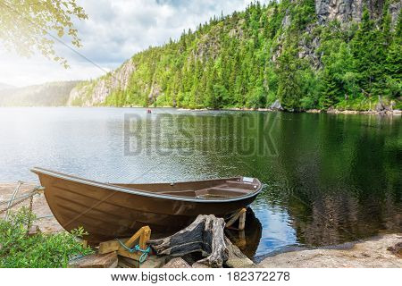 Wooden boat on the lake bank on forest background and blue sky reflecting in the surface of the river, Norway