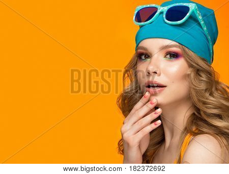Bright cheerful girl in a sports hat, colorful make-up, curls and pink manicure. Beauty face. Photo taken in the studio.