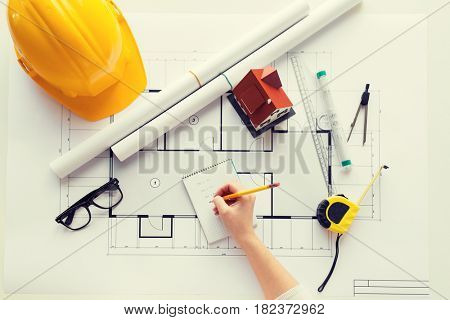 business, architecture, building, construction and people concept - close up of architect hand with blueprint and architectural tools writing to notebook
