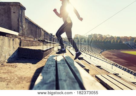 fitness, sport, exercising and people concept - close up of young woman running upstairs on stadium