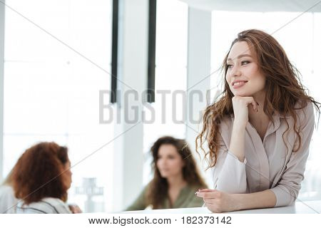 Smiling woman standing by the table in cafe with her friends on background
